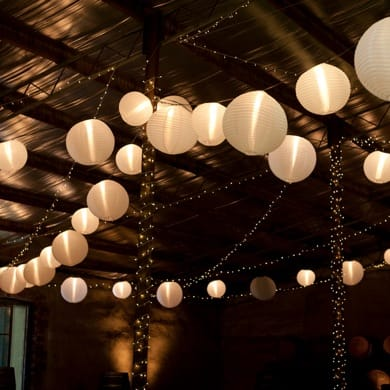 paper lanterns and fairy light strung up in a barn setting